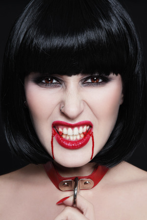 Young beautiful furious brunette with bloody vampire fangs and furious expression