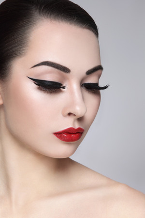 Portrait of young beautiful woman with stylish makeup. False eyelashes, black eyeliner and red lips