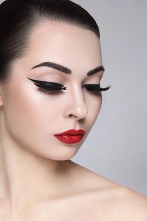 pestaÑas postizas: Retrato de joven bella mujer con estilo de maquillaje. Pestañas postizas, delineador de ojos y labios rojos negros