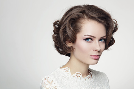 Portrait of young beautiful woman with curly prom hairdo in vintage style photo