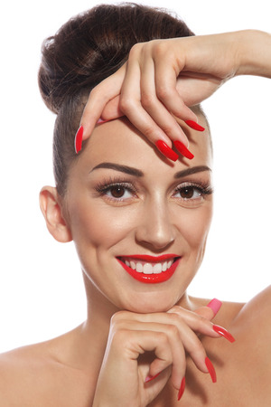 fake eyelashes: Portrait of young beautiful smiling girl with long red nails and lipstick over white background