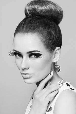 nailpolish: Black and white portrait of young beautiful woman with stylish make-up, hair bun and fancy polka dot manicure Stock Photo