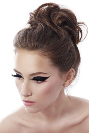 Young beautiful slom woman with fancy cat eye make-up and stylish hairdo over white background