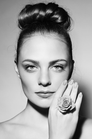nailpolish: Black and white portrait of young beautiful girl with trendy hair bun Stock Photo