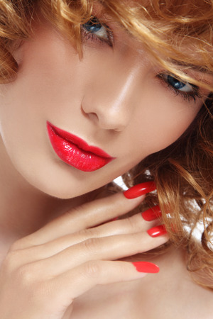 perming: Close-up portrait of young beautiful woman with stylish manicure and red lipstick over white background