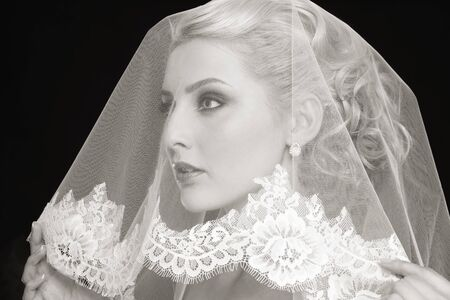bridal veil: Duotone portrait of young beautiful blonde bride with bridal veil over her face