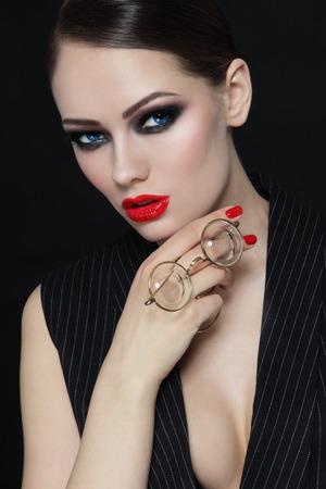 labios sexy: Mujer atractiva hermosa joven con maquillaje elegante y gafas de época en la mano