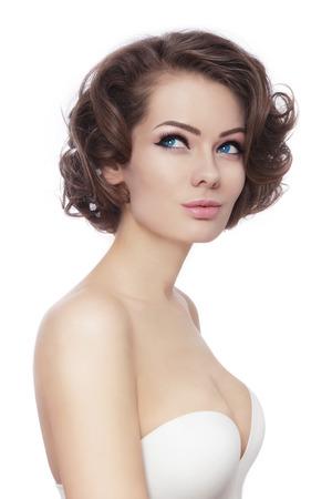 beaux seins: Belle jeune femme sexy avec �l�gante coiffure boucl�e regardant vers le haut sur fond blanc
