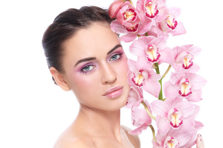 Young beautiful tanned healthy girl with clean pink make-up and orchid over white background photo