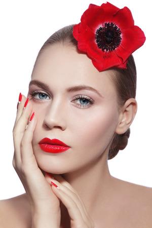 red lips: Mujer hermosa joven con la limpieza del maquillaje, labios rojos, manicura de fantasía y flor roja en la mano sobre fondo blanco Foto de archivo
