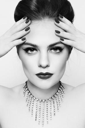 nailpolish: Black and white portrait of young beautiful woman with stylish make-up and manicure