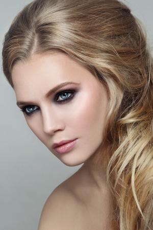 smoky eyes: Ritratto di giovane bella ragazza bionda con elegante pettinatura disordinato e occhi fumosi make-up