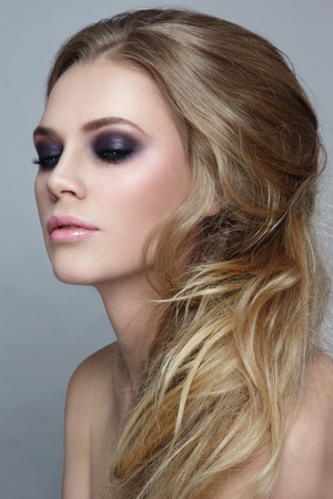 smoky eyes: Portrait of young beautiful blonde girl with stylish messy hairdo and smoky eyes make-up