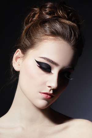 eye makeup: Young beautiful slim woman with fancy cat eye make-up and stylish hairdo