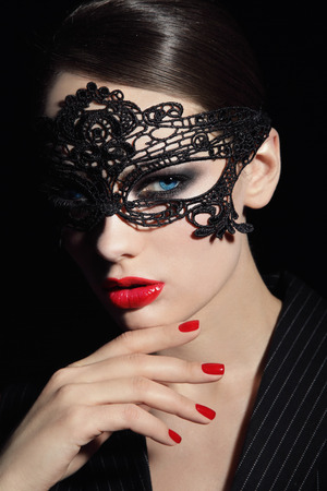 Portrait of young beautiful stylish woman in black lacy mask photo
