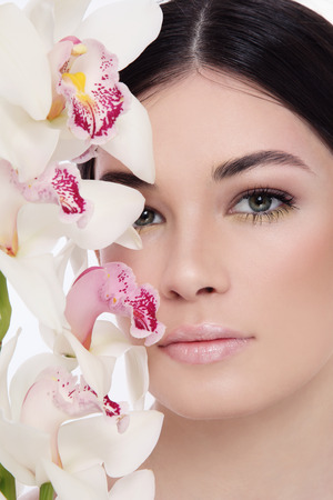 Close-up portrait of young beautiful woman with white orchid photo