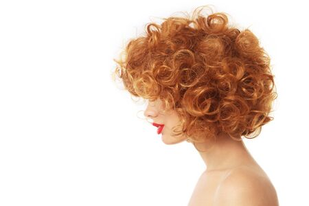 perming: Profile portrait of young woman with beautiful red curly hair over wite background
