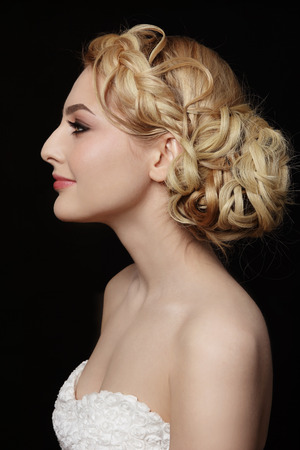 bride: Profile portrait of young beautiful blonde woman with stylish prom hairdo
