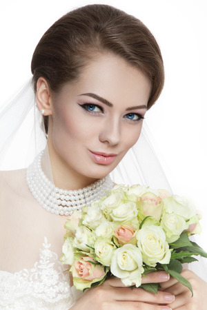 Young beautiful bride with stylish make-up and hairdo holding bouquet over white background photo