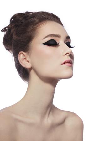 ojos negros: Joven y bella mujer delgada con lujo ojo de gato de maquillaje y peinado con estilo sobre fondo blanco