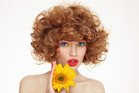 perming: Portrait of young beautiful woman with curly hair and sunflower in her hands Stock Photo