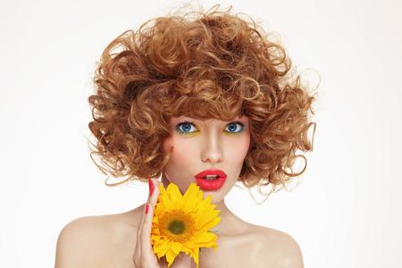 girasol: Retrato de joven bella mujer con el pelo rizado y girasol en sus manos