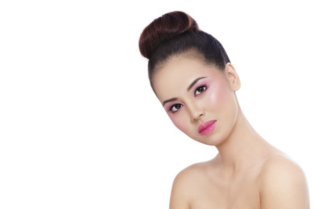cheekbones: Young beautiful healthy asian girl with shiny pink makeup and hair bun over white background, copy space