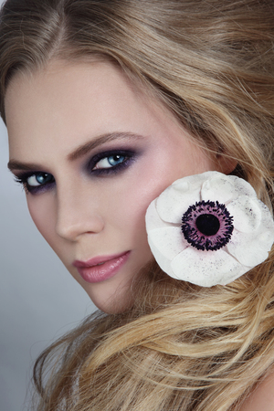 smoky eyes: Close-up portrait of young beautiful blonde girl with stylish violet smoky eyes make-up and messy hairdo
