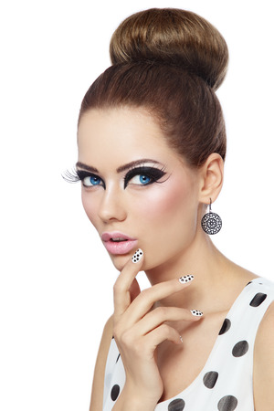 female eyes: Young beautiful girl with fancy cat eyes and polka dot manicure over white background Stock Photo