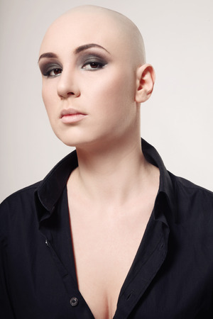 Portrait of young skinhead woman with smoky eyes make-up photo