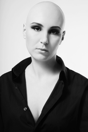 Black and white portrait of young skinhead woman with smoky eyes make-up photo