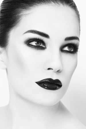 Black and white portrait of young beautiful woman with smoky eyes make-up photo