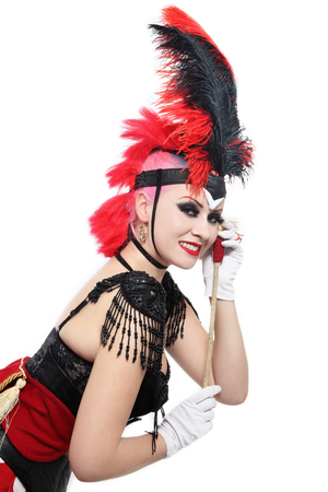 Pretty happy smiling bourlesque girl in fancy costume with plumage over white background photo