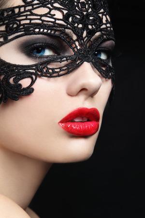블랙 레이스 마스크에서 젊은 아름 다운 세련 된 여자의 근접 초상화