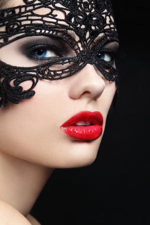Close-up portrait of young beautiful stylish woman in black lacy mask