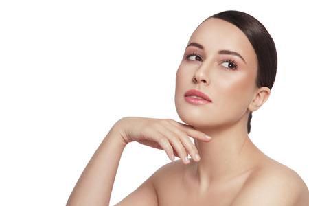 maquillage: Belle jeune femme heureuse saine toucher son visage et regardant vers le haut sur fond blanc, copie, espace