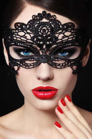 Portrait of young beautiful blue-eyed woman in black lacy mask Standard-Bild