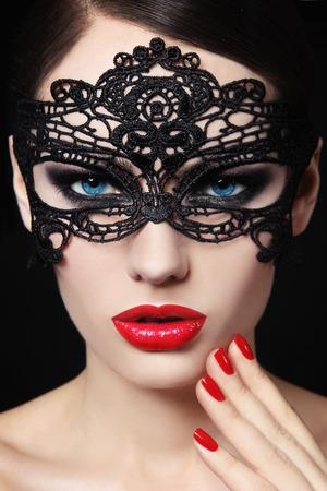 Portret van een jonge mooie blue-eyed vrouw in het zwart kanten masker