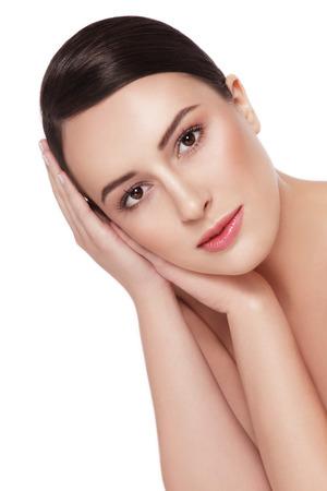 Junge schöne gesunde glückliche Frau berührt ihr Gesicht auf weißem Hintergrund