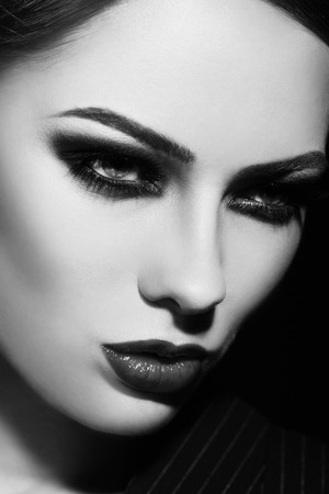 smoky: Black and white close-up portrait of young beautiful woman with smoky eyes