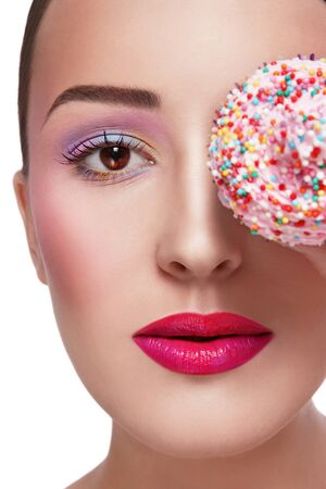 guilty pleasure: Close-up portrait of young beautiful girl with stylish make-up and colorful cupcake, over white background