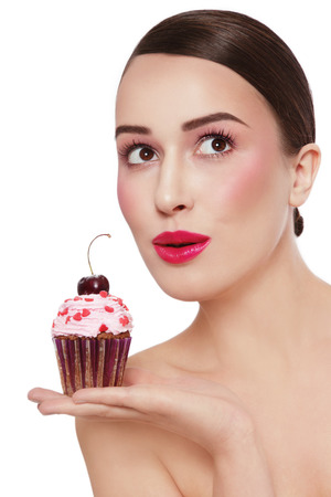 guilty pleasure: Young beautiful girl with excited expression and tasty cupcake in her hand looking upwards over white background