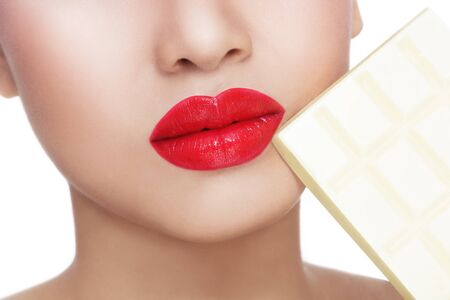guilty pleasure: Close-up shot of beautiful woman lips with white chocolate bar