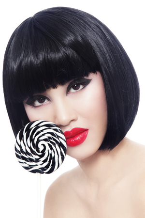 guilty pleasure: Portrait of young beautiful asian girl with red lipstick and fancy striped lollipop over white background Stock Photo