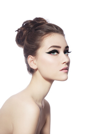 hairdo: Young beautiful slim woman with fancy cat eye make-up and stylish hairdo over white background
