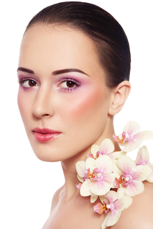 Portrait of young beautiful woman with glowing make-up and orchid over white background