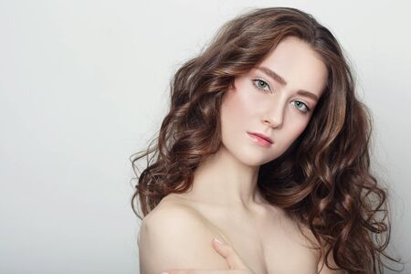 Portrait of young beautiful girl with clear skin and long healthy curly hair Stock Photo