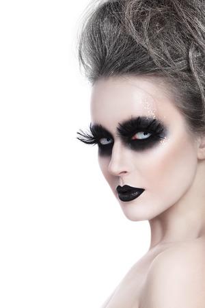 white feather: Mujer joven con el estilo de fantasía gótica de Halloween maquillaje y peinado sobre fondo blanco, espacio de la copia