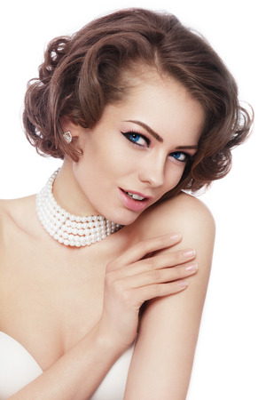 Young beautiful sexy woman with stylish curly hairdo and pearl nacklace over white background, copy space
