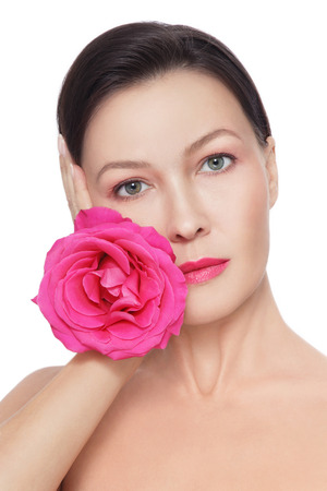 Portrait of young beautiful healthy mature woman with fancy pink rose over white background Stock Photo